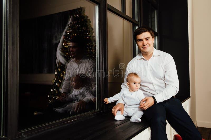 Gelukkige vader met zijn één éénjarige zoon het spelen thuis op het bed royalty-vrije stock afbeeldingen