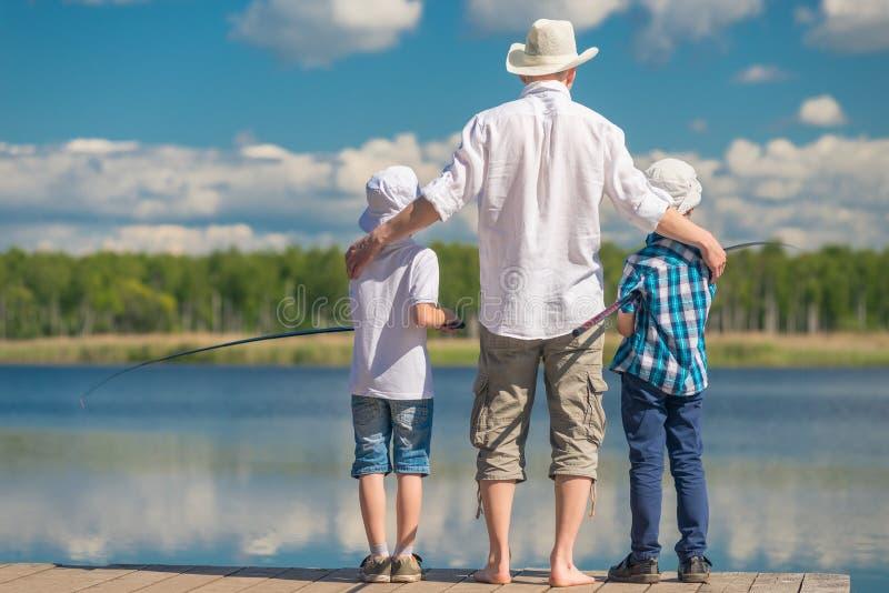 gelukkige vader met zonen op een visreis royalty-vrije stock afbeeldingen