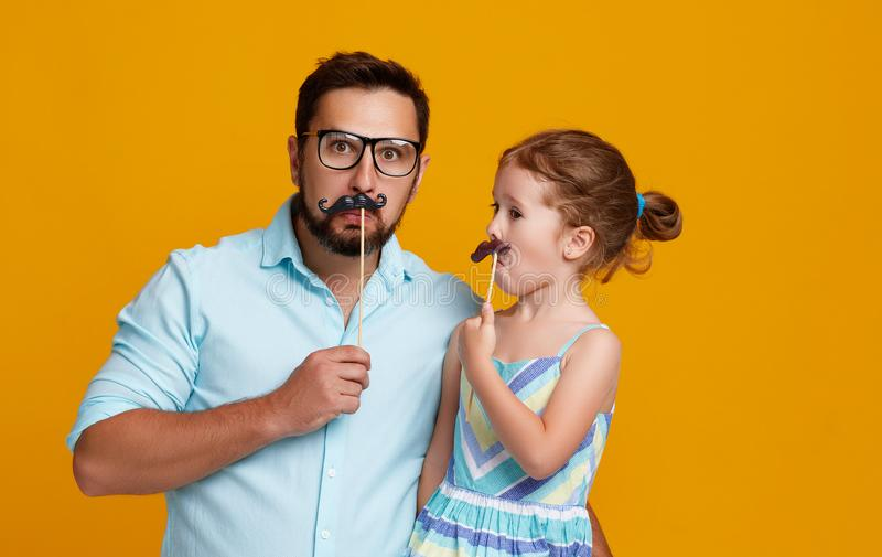 Gelukkige vader` s dag! grappige papa en dochter met snor het voor de gek houden royalty-vrije stock afbeelding