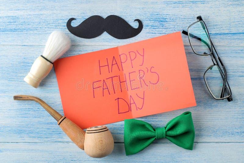 Gelukkige Vader` s dag tekst en van mensen toebehoren, vlinderdas en rokende pijp en glazen op een lichtblauwe houten achtergrond stock fotografie