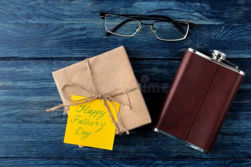 Gelukkige Vader` s dag Tekst op document, gift, glazen en fles op een blauwe houten lijst de vakantie van mensen Hoogste mening stock afbeelding