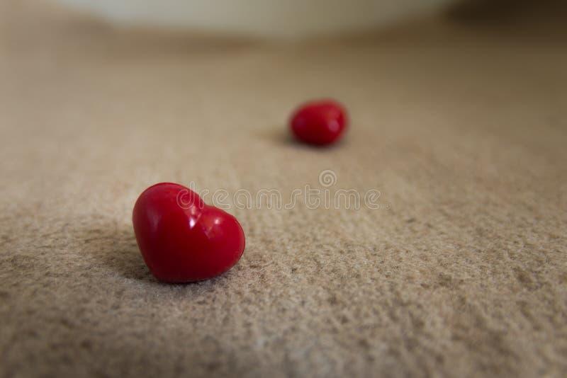 Gelukkige valentijnskaart dag twee rode harten op lichtbruin Tapijt royalty-vrije stock foto