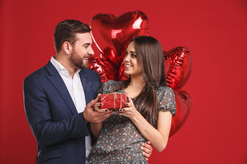 Gelukkige valentijnskaartendag De jongen geeft een gift aan zijn meisje stock afbeelding
