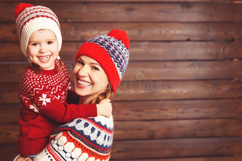 Gelukkige van het familiemoeder en kind meisjesomhelzingen bij houten achtergrond royalty-vrije stock foto