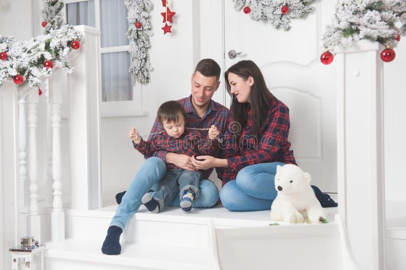 Gelukkige van het huiselijke manvrouw en kind zitting op portiek van Kerstmis D royalty-vrije stock afbeeldingen