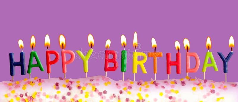 Gelukkige verjaardag aangestoken kaarsen op purpere achtergrond stock afbeeldingen