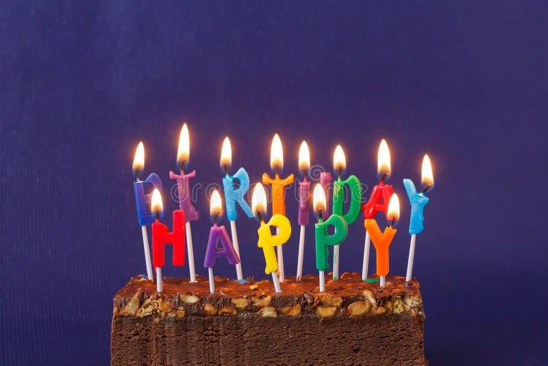 Gelukkige Verjaardag Brownie Cake met Pinda's, Gezouten Karamel en Kleurrijke Brandende Kaarsen op Violet Background Exemplaarrui royalty-vrije stock fotografie