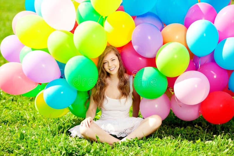 Gelukkige verjaardagsvrouw tegen de hemel met regenboog-gekleurde luchtbedelaars stock fotografie