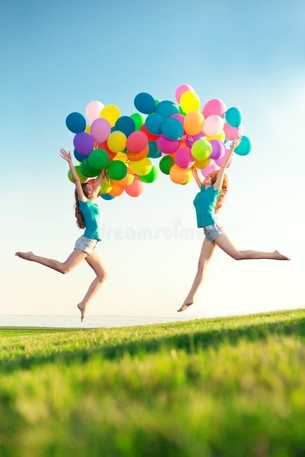 Gelukkige verjaardagsvrouwen tegen de hemel met regenboog-gekleurde luchtbedelaars stock foto's