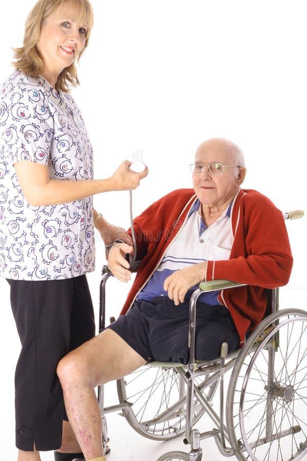 Gelukkige verpleegster die bejaarde patiënt controleert stock foto's