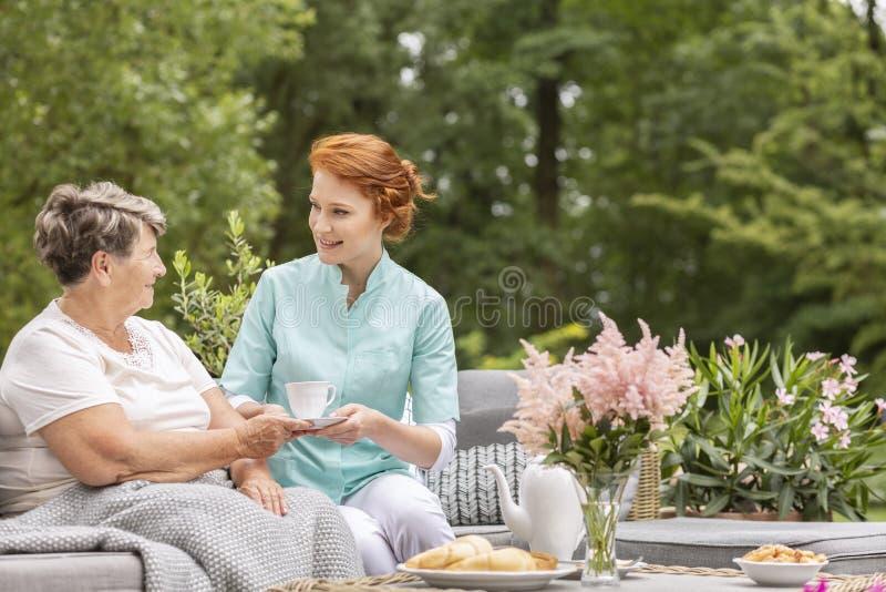 Gelukkige verpleegster die thee geven aan bejaarde terwijl het eten van ontbijt o stock foto