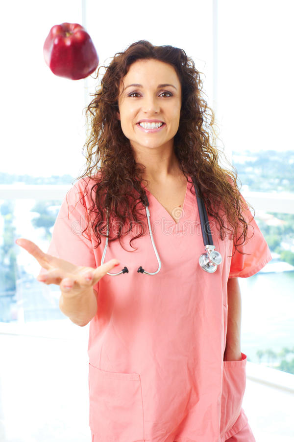Gelukkige Verpleegster Throwing Apple In de Lucht royalty-vrije stock afbeeldingen