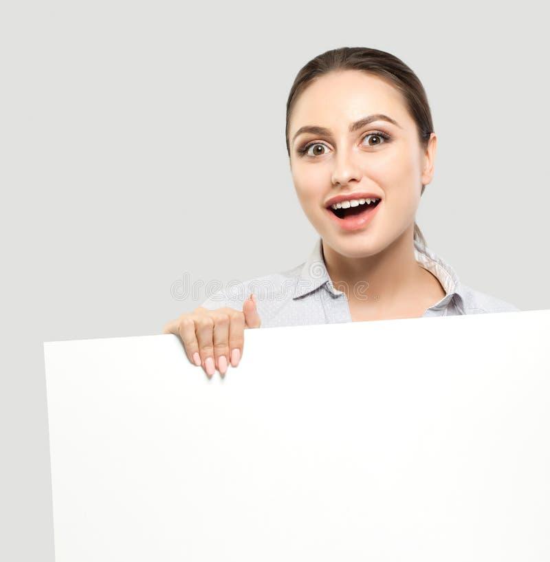 Gelukkige verraste onderneemster met witte lege raadsachtergrond Jong vrolijk vrouwen, bedrijfs en onderwijsconcept royalty-vrije stock afbeelding