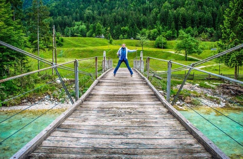 Gelukkige verre vrouwensprong van een houten voetbrugvoetgangersbrug over rivier Soca in Slovenië op wilde aardachtergrond royalty-vrije stock fotografie