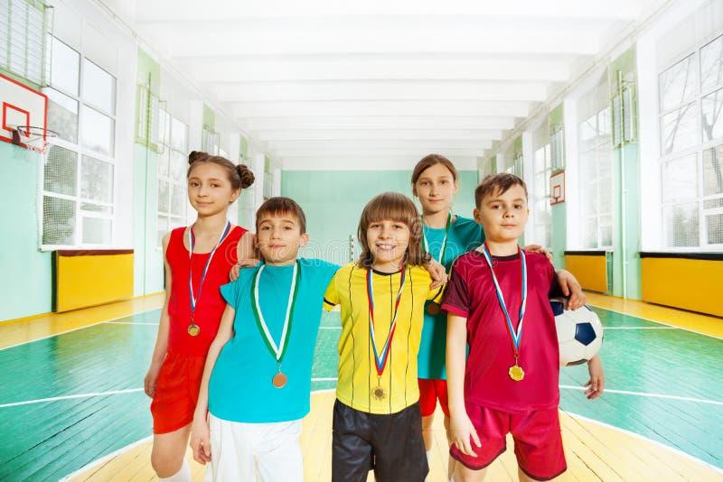 Gelukkige voetbalwinnaars met medailles in sporthal stock afbeelding