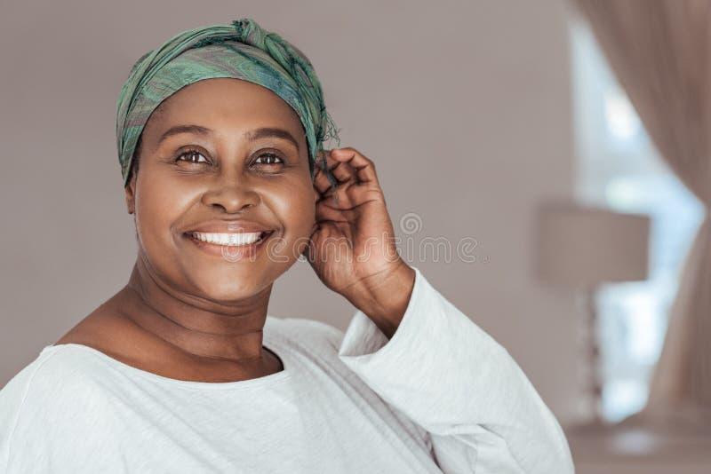 Gelukkige volwassen Afrikaanse vrouw die op een modieuze headscarf dragen royalty-vrije stock afbeelding