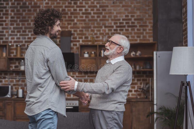gelukkige volwassen zoon en hogere vader het schudden handen stock foto's