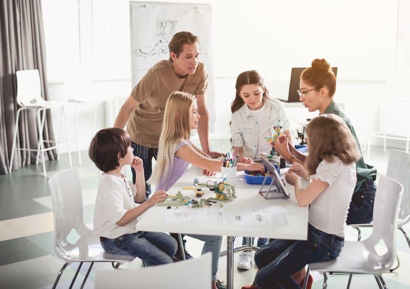 Gelukkige volwassenen die stuk speelgoed met kinderen maken royalty-vrije stock afbeeldingen