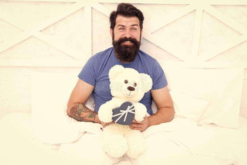 Gelukkige volwassenheid home shopping - concept Liefde en geluk bebaarde man teddy beer in bed Cadeaudoos voor feestdagen leuk royalty-vrije stock foto