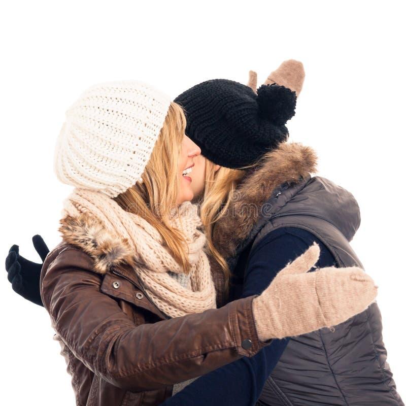 Gelukkige vrienden in de winterkleren het begroeten royalty-vrije stock afbeeldingen