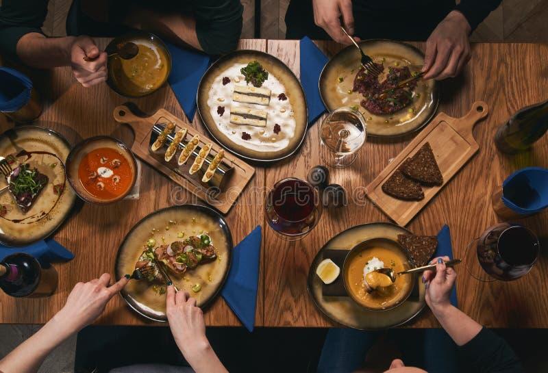 Gelukkige vrienden die aardige voedsel en dranken hebben stock fotografie