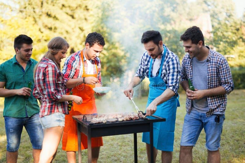 Gelukkige vrienden die barbecue van partij genieten royalty-vrije stock afbeeldingen