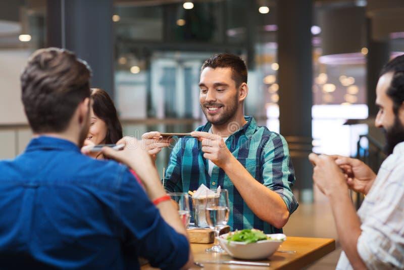 Gelukkige vrienden die beeld van voedsel nemen bij restaurant royalty-vrije stock foto