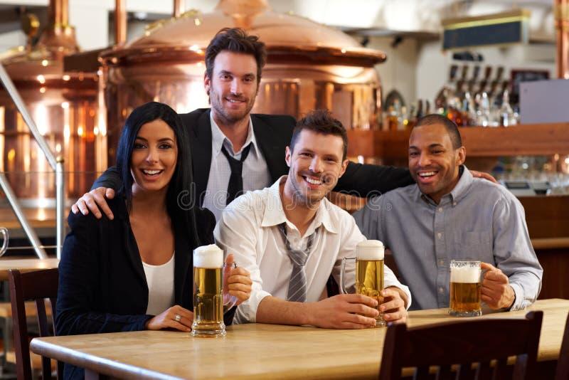 Gelukkige vrienden die bier drinken bij bar stock fotografie