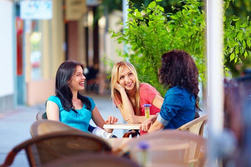 Gelukkige vrienden die in de zomerkoffie spreken, in openlucht stock afbeeldingen