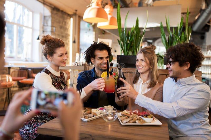 Gelukkige vrienden die dranken clinking bij bar of koffie stock fotografie