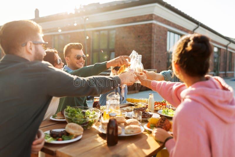 Gelukkige vrienden die dranken roosteren bij dakpartij royalty-vrije stock afbeelding
