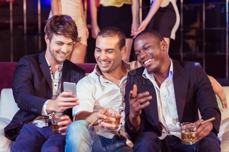 Gelukkige vrienden die een smartphone gebruiken royalty-vrije stock fotografie