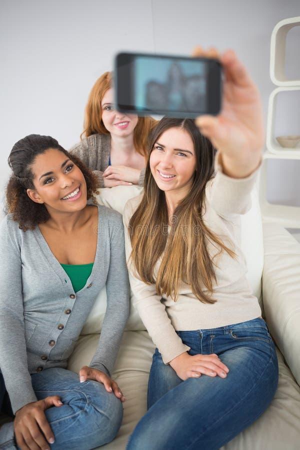 Gelukkige vrienden die fotograferen met smartphone stock foto's