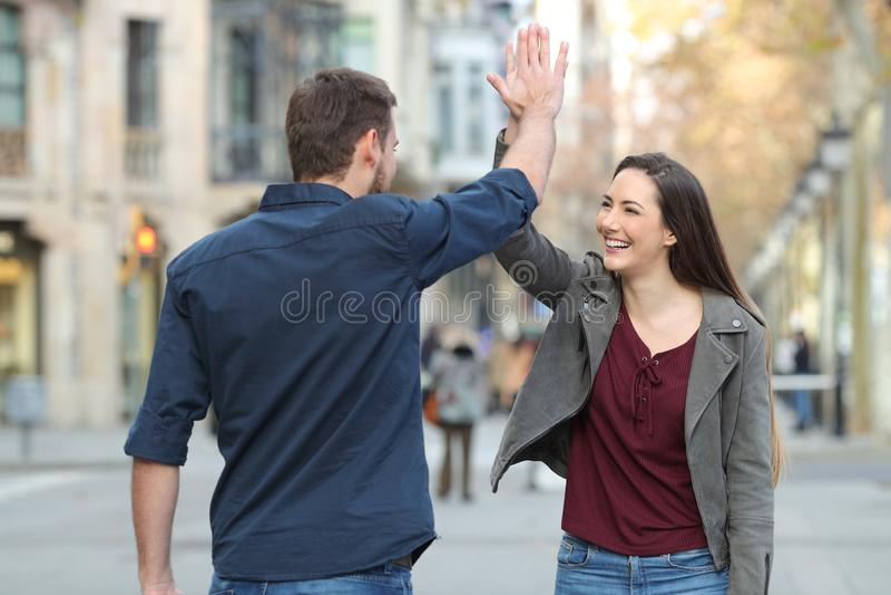 Gelukkige vrienden die hoogte vijf in de straat geven royalty-vrije stock fotografie
