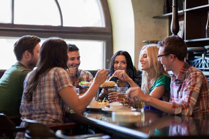 Gelukkige vrienden die met bier bij bar of bar eten stock foto's