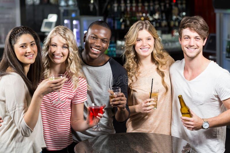 Gelukkige vrienden die met bier en cocktails roosteren stock afbeelding