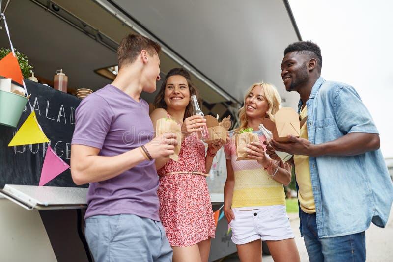 Gelukkige vrienden die met dranken bij voedselvrachtwagen eten stock afbeelding