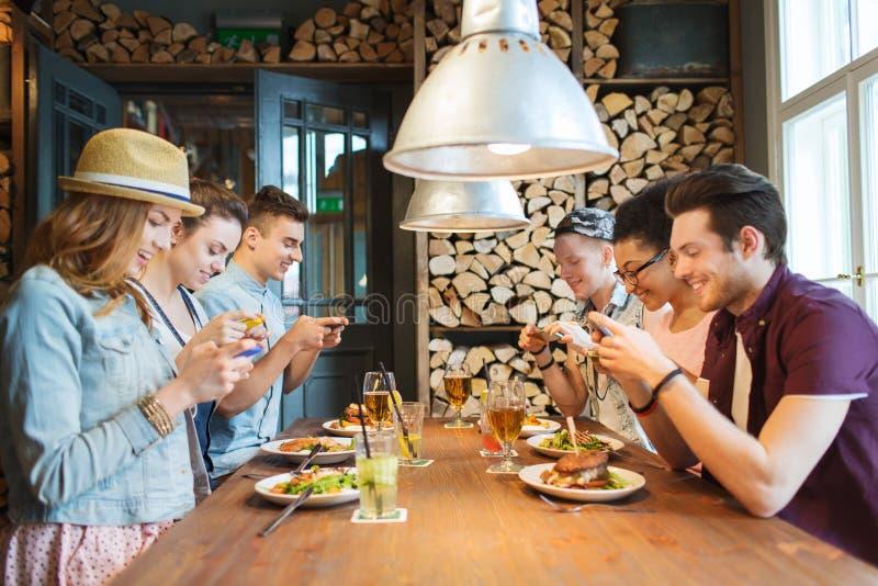 Gelukkige vrienden die met smartphones voedsel voorstellen stock foto's