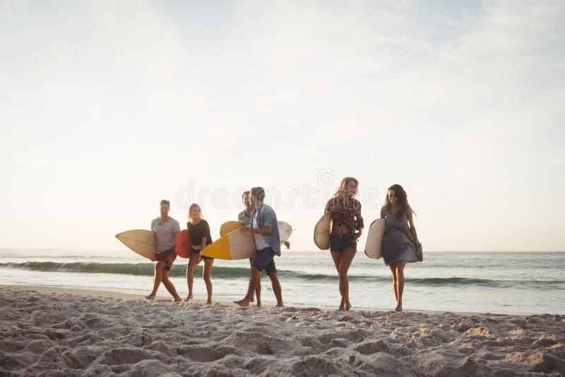 Gelukkige vrienden die met surfplanken lopen royalty-vrije stock fotografie