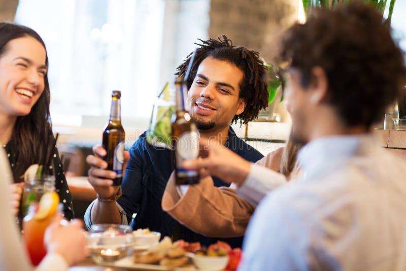 Gelukkige vrienden die niet alcoholisch bier drinken bij bar stock foto