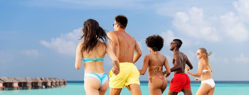Gelukkige vrienden die op de zomerstrand lopen stock foto