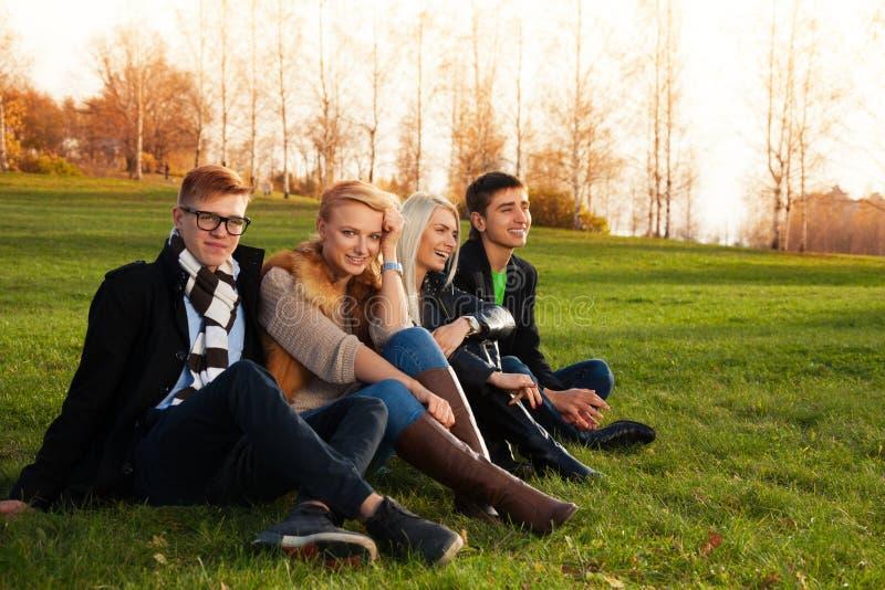 Gelukkige vrienden die op groen gras zitten stock foto