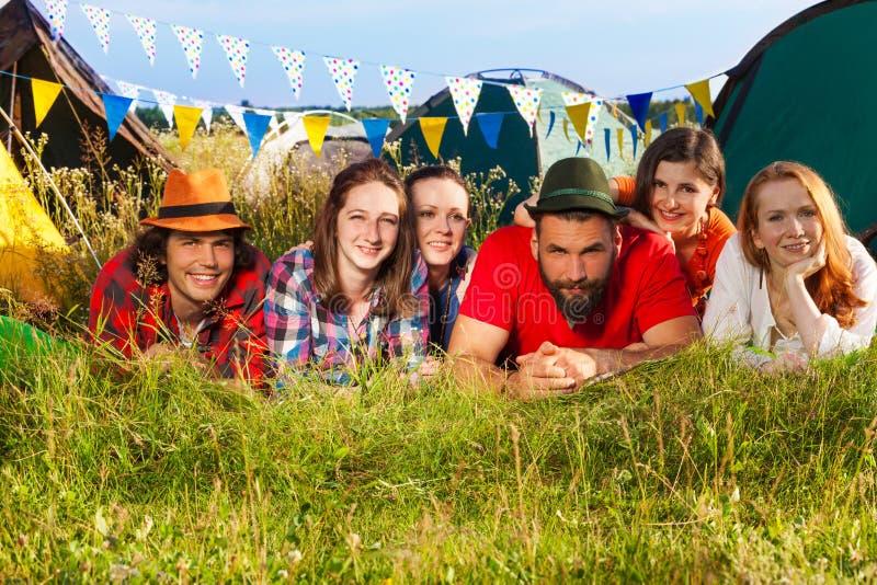 Gelukkige vrienden die op het gras bij kampeerterrein liggen stock afbeelding
