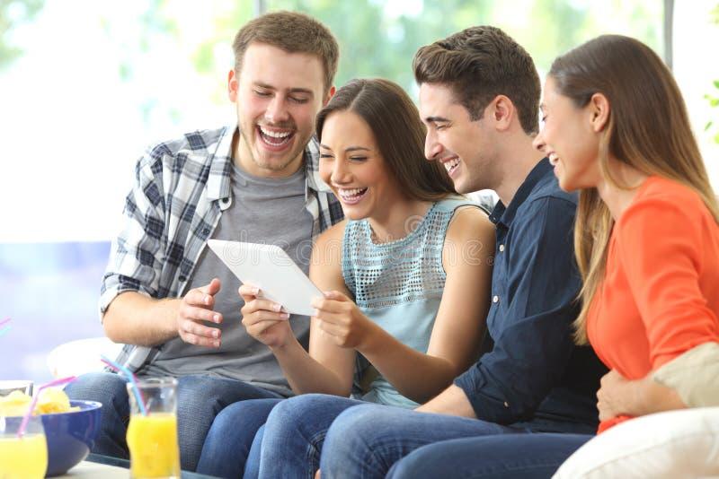 Gelukkige vrienden die op media in een tablet letten stock foto's