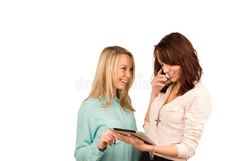 Gelukkige vrienden die over een tablet lachen stock fotografie