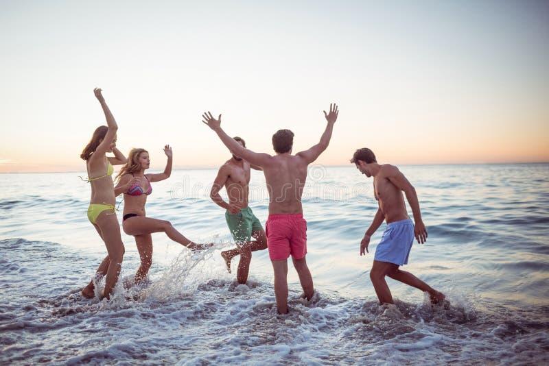 Gelukkige vrienden die pret in het water hebben stock fotografie
