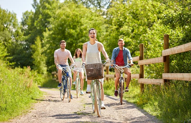Gelukkige vrienden die staand vistuigfietsen in de zomer berijden stock foto's