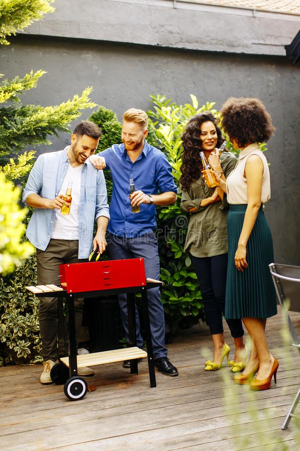 Gelukkige vrienden die voedsel roosteren en barbecue van partij in openlucht genieten royalty-vrije stock foto