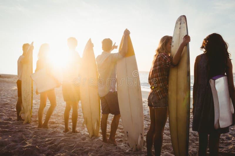 Gelukkige vrienden die zich overeenkomstig surfplanken bevinden stock afbeeldingen