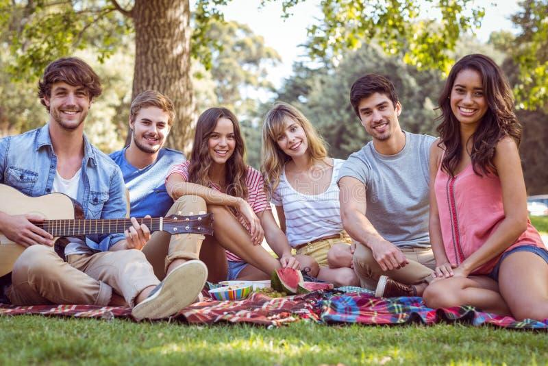 gelukkige vrienden in een park die een picknick hebben royalty-vrije stock afbeeldingen